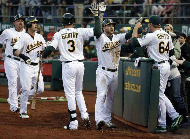 Oakland Athletics' Brett Lawrie (15) is high-fived by A.J. Griffin (64) and Craig Gentry (3) after Lawrie's three-run home run against the Los Angeles Angels during the first inning of a baseball game Tuesday, April 28, 2015, in Oakland, Calif. (AP Photo/Marcio Jose Sanchez)