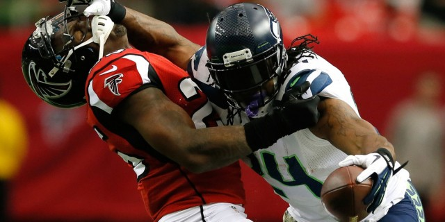 ATLANTA, GA - NOVEMBER 10:  Marshawn Lynch #24 of the Seattle Seahawks stiff arms William Moore #25 of the Atlanta Falcons at Georgia Dome on November 10, 2013 in Atlanta, Georgia.  (Photo by Kevin C. Cox/Getty Images)