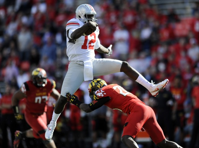 Ohio State's quarterback Cardale Jones leaps over Maryland's safety Anthony Nixon during the second half of an NCAA college football game in College Park, Md., Saturday, Oct. 4, 2014. Ohio State won 52-24.(AP Photo/Gail Burton)