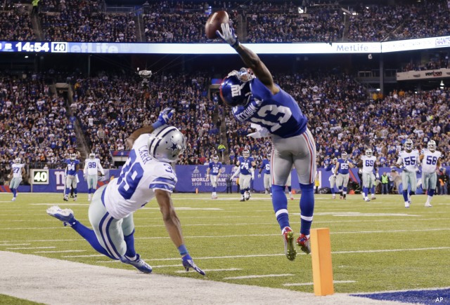 New York Giants wide receiver Odell Beckham Jr. (13) makes a one-handed catch for a touchdown against Dallas Cowboys cornerback Brandon Carr (39) in the second quarter of an NFL football game, Sunday, Nov. 23, 2014, in East Rutherford, N.J. (AP Photo/Julio Cortez)  ORG XMIT: ERU108
