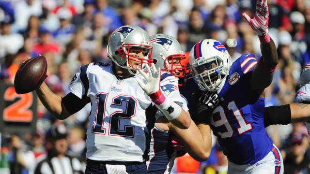 New England Patriots quarterback Tom Brady (12) is rushed by Buffalo Bills defensive end Manny Lawson (91) during the first half of an NFL football game Sunday, Oct. 12, 2014, in Orchard Park, N.Y. (AP Photo/Gary Wiepert)
