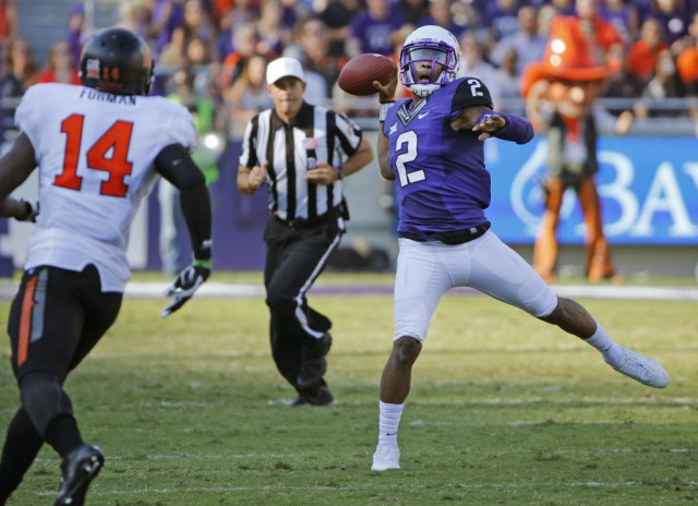 TCU quarterback Trevone Boykin (2) throws a second-quarter pass as OSU's Josh Furman (14) watches during the Oklahoma State University Cowboys vs. the TCU Horned Frogs college football game at Amon G. Carter Stadium in Fort Worth on Saturday, October 18, 2014.  (Louis DeLuca/The Dallas Morning News)