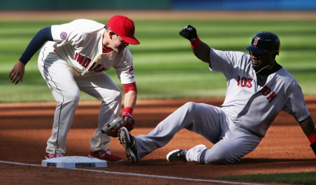Boston Red Sox's David Ortiz, right, is tagged out by Cleveland Indians' Giovanny Urshela while attempting to steal third base during the first inning of a baseball game, Sunday, Oct. 4, 2015, in Cleveland. (AP Photo/Ron Schwane)