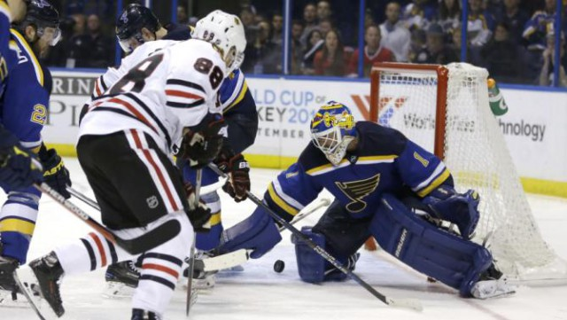 Chicago Blackhawks' Patrick Kane, left, shoots on St. Louis Blues goalie Brian Elliott during the second overtime in Game 5 of an NHL hockey first-round Stanley Cup playoff series early Friday, April 22, 2016, in St. Louis. Kane skated behind the net and scored moments later. The Blackhawks won 4-3. (AP Photo/Jeff Roberson)