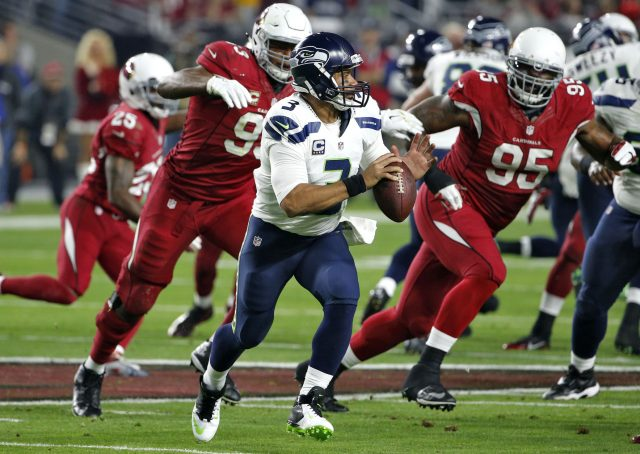 Seattle Seahawks quarterback Russell Wilson (3) looks to throw as Arizona Cardinals defensive end Tommy Kelly (95) and Calais Campbell (93) pursue during the first half of an NFL football game, Sunday, Dec. 21, 2014, in Glendale, Ariz. (AP Photo/Ross D. Franklin)