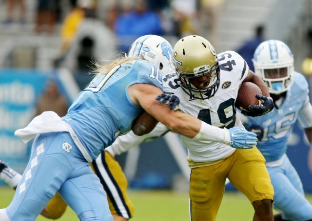 Oct 3, 2015; Atlanta, GA, USA; Georgia Tech Yellow Jackets running back Clinton Lynch (49) runs for a first down as he is stopped by North Carolina Tar Heels linebacker Jeff Schoettmer (10) in the first quarter of their game at Bobby Dodd Stadium. Mandatory Credit: Jason Getz-USA TODAY Sports