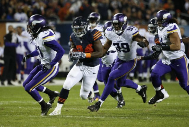 Chicago Bears running back Jordan Howard (24) runs from Minnesota Vikings strong safety Anthony Harris, from left, Danielle Hunter (99) and Eric Kendricks (54) during the first half of an NFL football game in Chicago, Monday, Oct. 31, 2016. (AP Photo/Nam Y. Huh) ORG XMIT: ILPS111